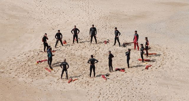 group of lifeguards in a circle on the beach