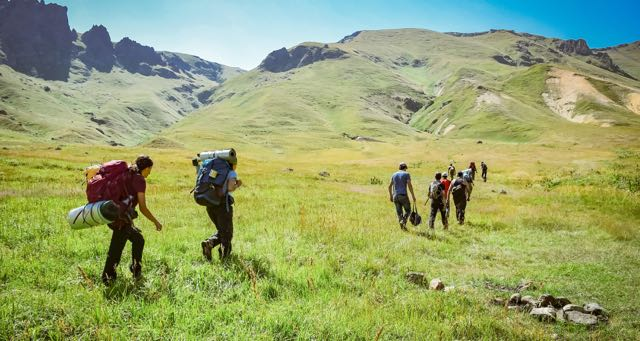 group of people hiking in a green mountain