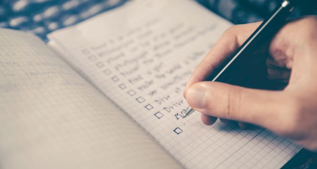 making a checklist on a notepad